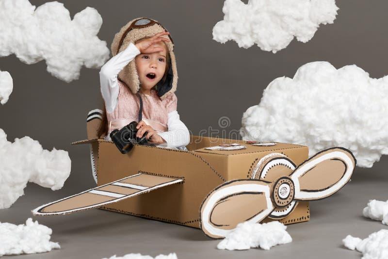 A menina da criança joga em um avião feito da caixa de cartão e dos sonhos de transformar-se um piloto, nuvens do algodão em um b imagem de stock