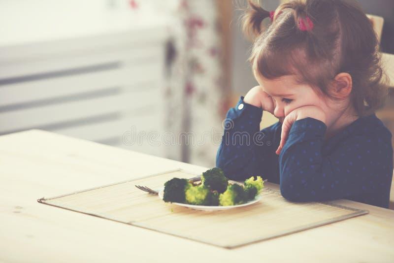 A menina da criança não gosta e não os quer de comer de vegetais fotos de stock royalty free