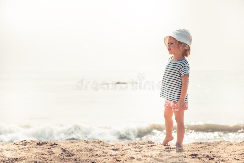 Menina da criança da criança na praia que olha na distância que procura por algo com estilo de vida feliz da infância do conceito fotografia de stock royalty free