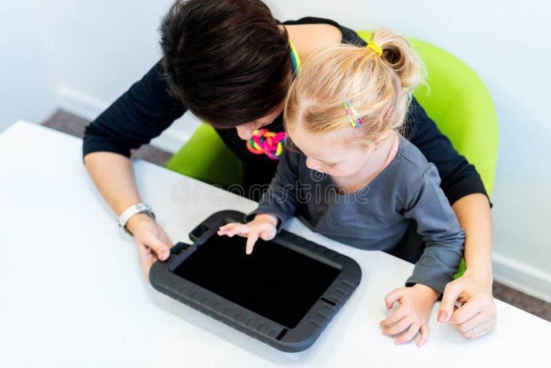 Menina da criança na sessão de terapia ocupacional da criança que faz exercícios brincalhão sensoriais com seu terapeuta que usa  fotografia de stock