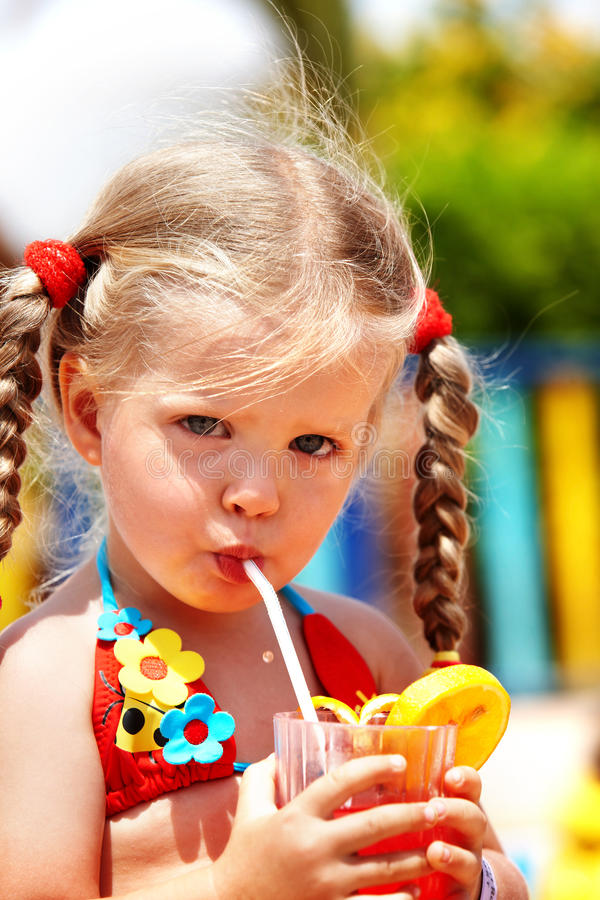 Menina da criança no sumo de laranja vermelho da bebida do biquini. imagem de stock royalty free