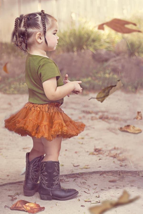 Menina da criança no tutu alaranjado e em botas de vaqueiro pretas fotografia de stock