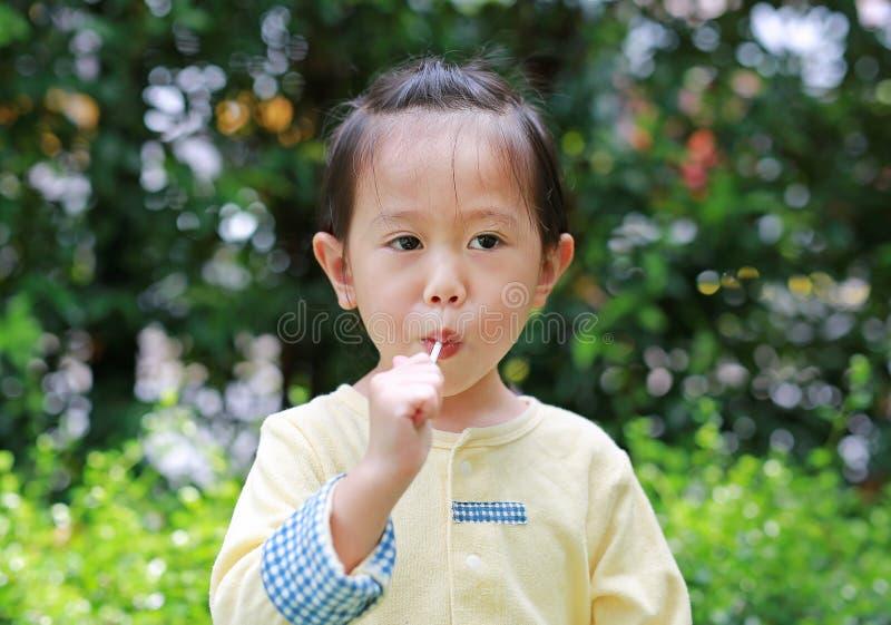 A menina da criança pequena aprecia comer doces do pirulito no parque fotografia de stock