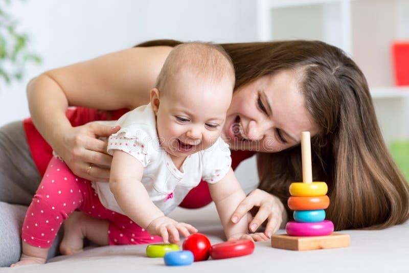 A menina da criança pequena e sua mamã jogam com brinquedos da cor em casa imagem de stock royalty free