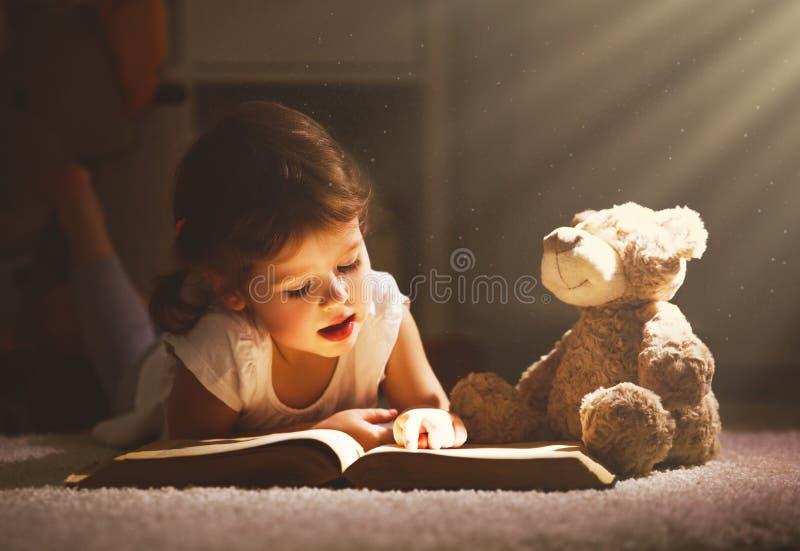 A menina da criança pequena está lendo um livro na noite na obscuridade com o à fotos de stock royalty free