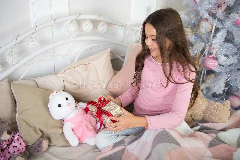 A menina da criança pequena gosta do presente do xmas Natal A criança aprecia o feriado Ano novo feliz menina feliz pequena no Na imagens de stock