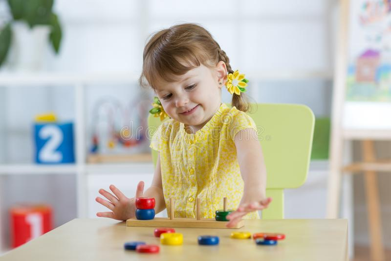 A menina da criança pequena joga no jardim de infância na classe do pré-escolar de Montessori fotografia de stock