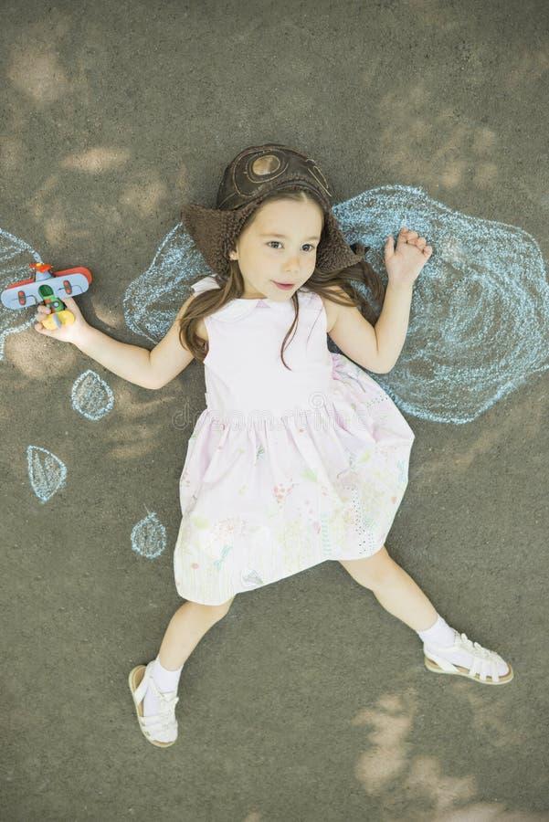 A menina da criança pequena joga o astronauta fotografia de stock royalty free