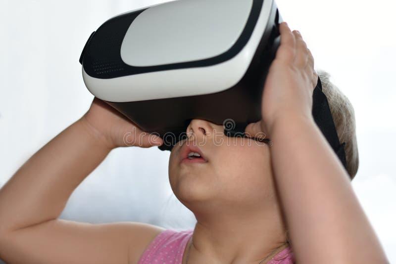 A menina da criança pequena joga um jogo com vidros da realidade virtual no fundo branco, realidade aumentada, capacete, jogo de  fotos de stock royalty free
