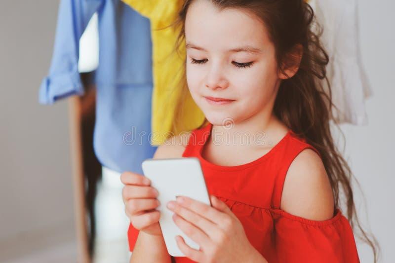 menina da criança pequena que faz o selfie ao tentar na roupa nova em sua sala apropriada do vestuário ou da loja imagem de stock royalty free