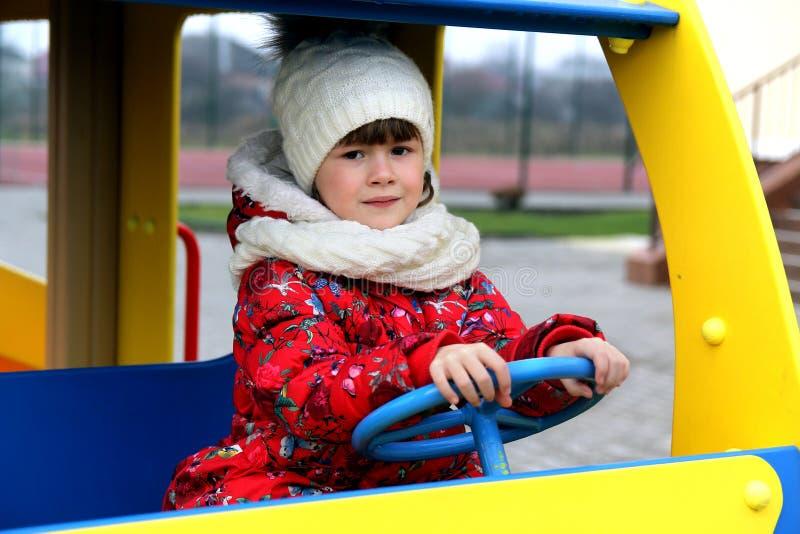 Menina da criança pequena que joga no campo de jogos fora no carro imagem de stock