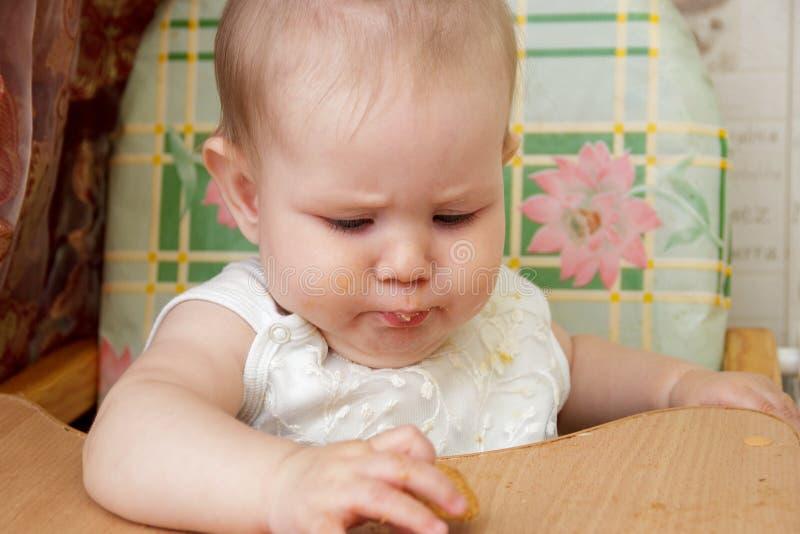 A menina da criança pequena senta-se em um cadeirão e come-se cookies imagens de stock