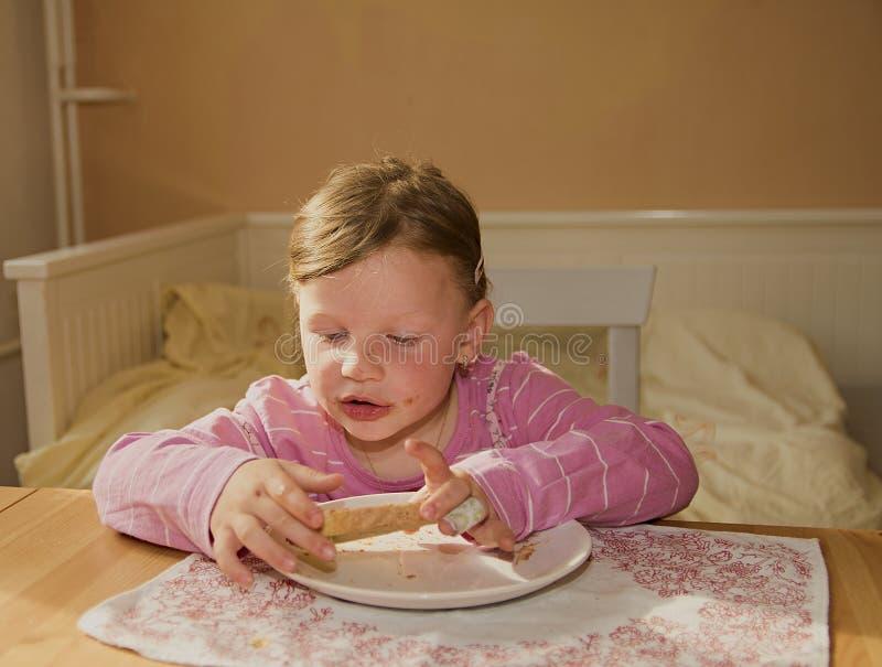 A menina da criança playlful come o creme do chocolate espalhado no pão Petisco doce do alimento do chocolate A menina feliz tem  imagem de stock royalty free