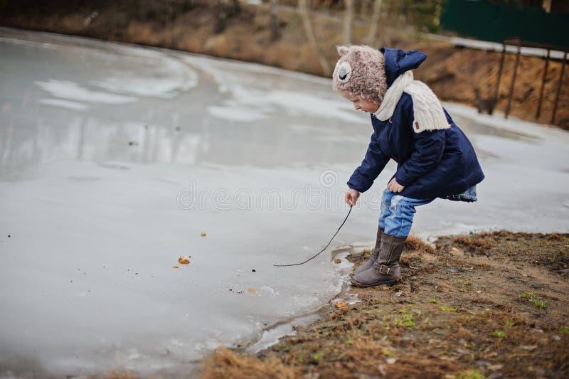 Menina da criança que anda no lago congelado, começado derreter no dia de mola adiantado fotografia de stock royalty free