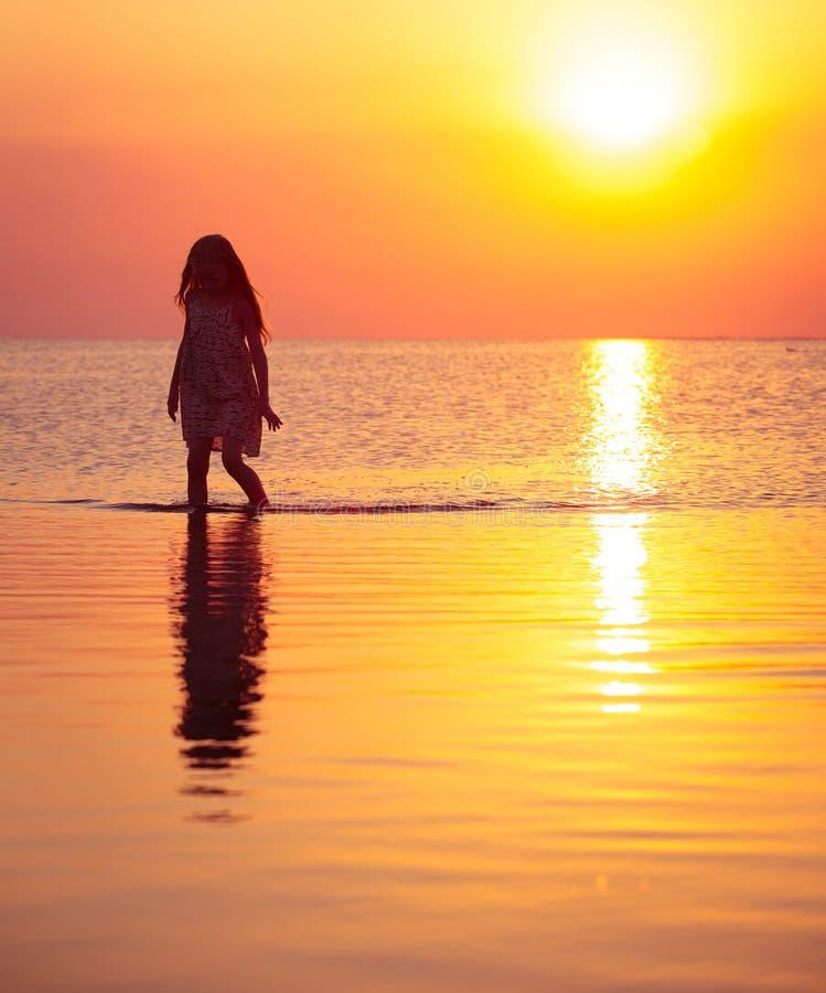 Menina da criança que anda no mar do por do sol fotos de stock royalty free
