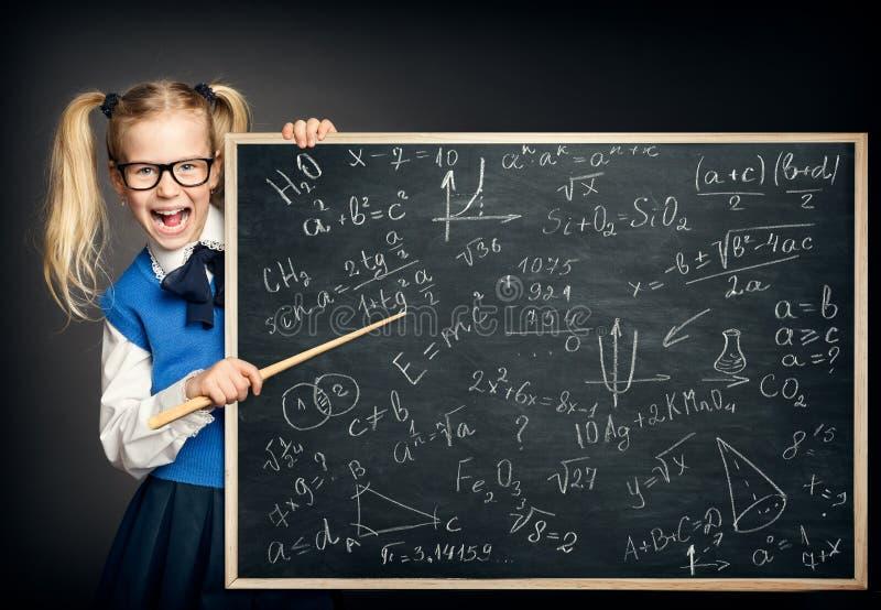 Menina da criança que aponta o quadro-negro com fórmulas da matemática, criança surpreendida da escola como o professor fotos de stock royalty free