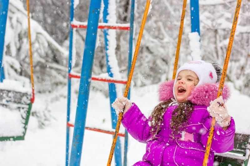 Menina da criança que balança no parque do inverno imagens de stock royalty free