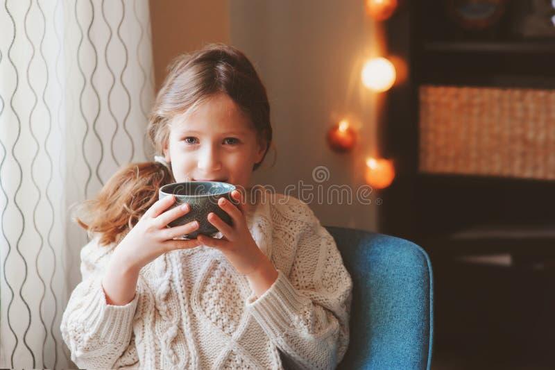 Menina da criança que bebe o cacau quente em casa no fim de semana do inverno, sentando-se na cadeira acolhedor fotos de stock