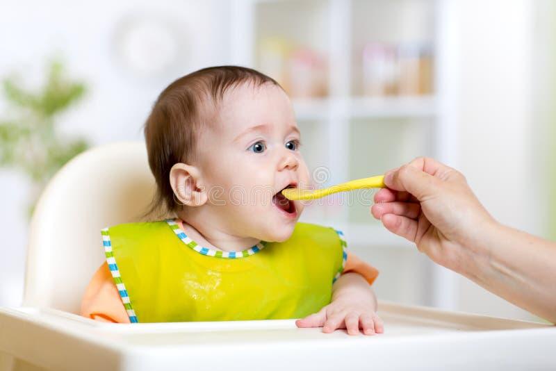 Menina da criança que come com colher dentro imagem de stock