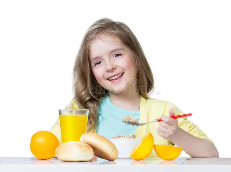 Menina da criança que come na tabela isolada no branco imagens de stock royalty free