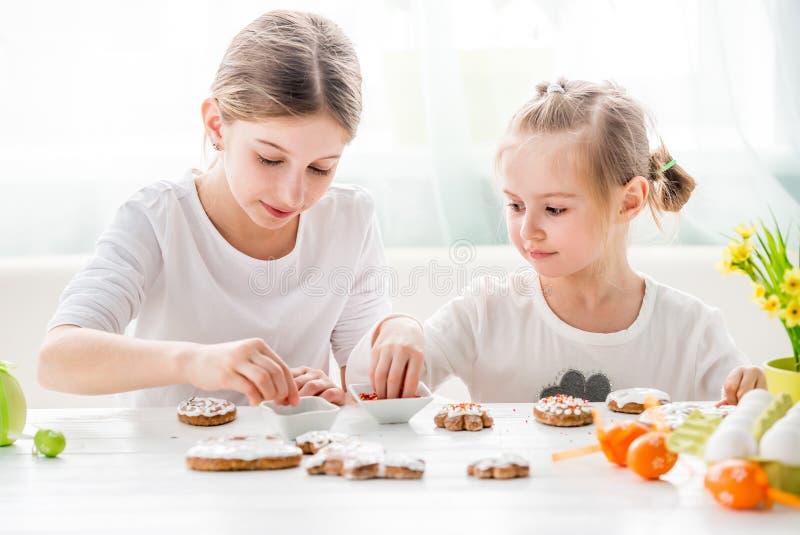 Menina da criança que decora cookies da Páscoa imagem de stock