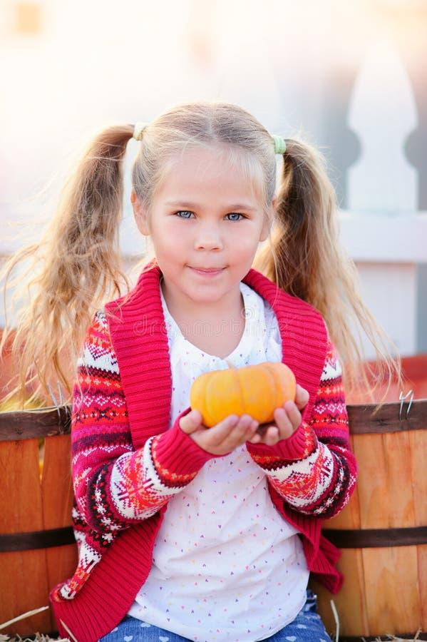 Menina da criança que escolhe uma abóbora para Dia das Bruxas fotografia de stock royalty free