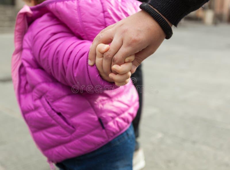 Menina da criança que guarda as mãos com sua mãe fotografia de stock