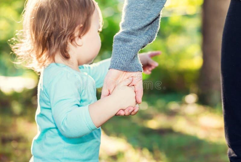 Menina da criança que guarda as mãos com sua mãe imagem de stock
