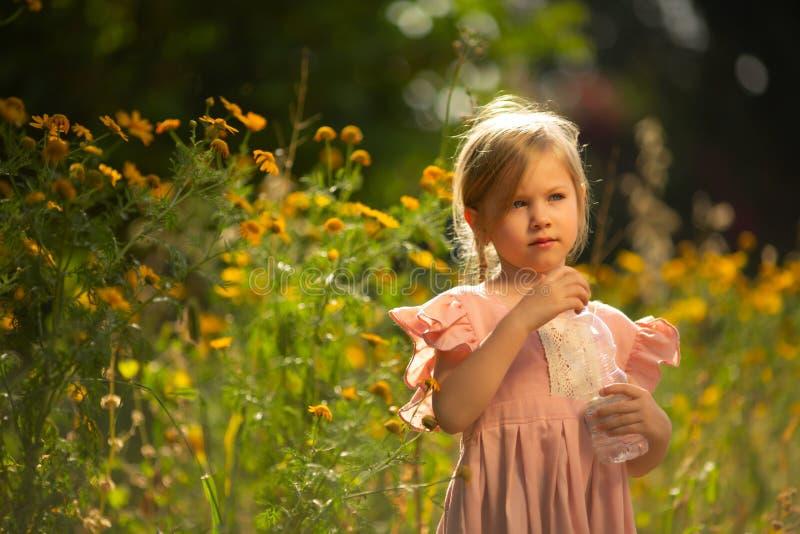 Menina da criança que guarda a garrafa da água foto de stock royalty free