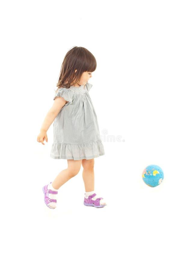 Menina da criança que joga com globo do mundo imagens de stock royalty free