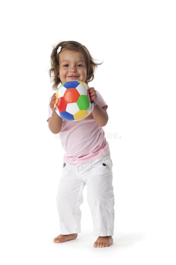 Menina da criança que joga com uma esfera colorida fotografia de stock royalty free