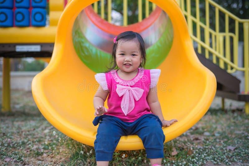 Menina da criança que joga em uma corrediça no campo de jogos das crianças imagem de stock