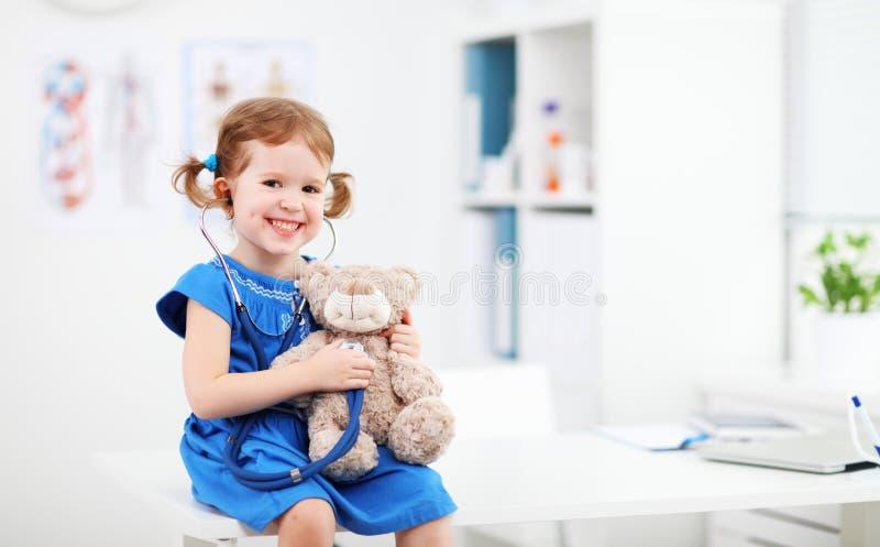 Menina da criança que joga o doutor com urso de peluche imagens de stock