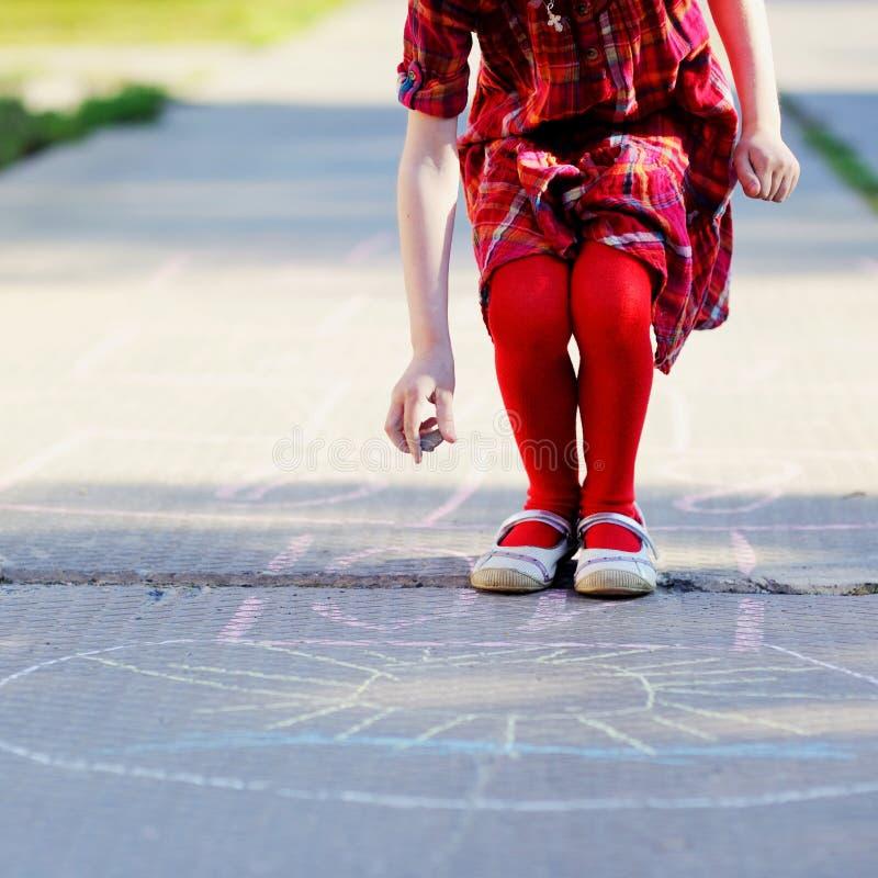 Menina da criança que joga o hopscotch no asfalto imagem de stock