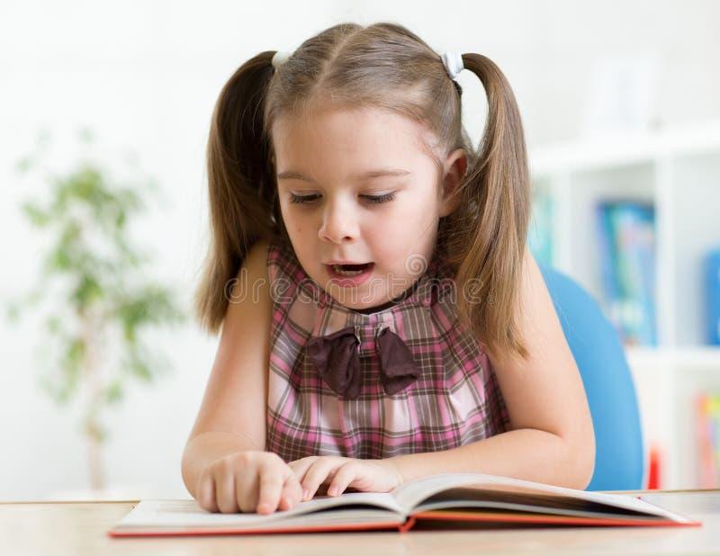 Menina da criança que lê um livro em casa fotos de stock royalty free