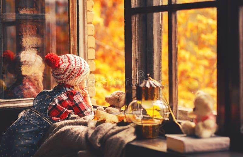 Menina da criança que olha através da janela aberta no outono da natureza imagem de stock