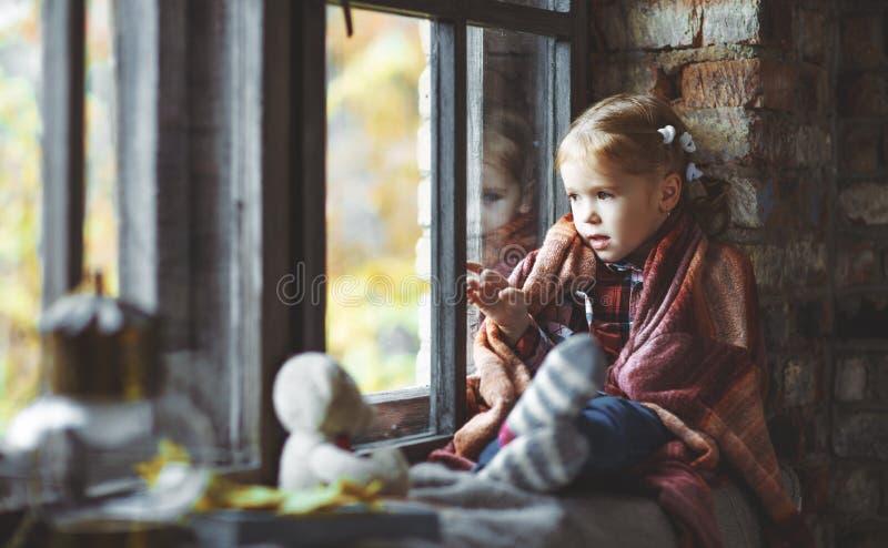 Menina da criança que olha através da janela no outono da natureza fotografia de stock royalty free