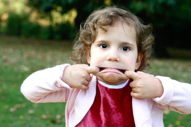 Menina da criança que puxa as faces engraçadas imagens de stock