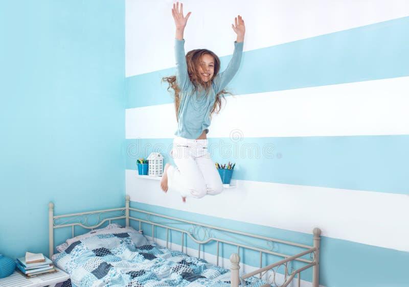 Menina da criança que salta na cama fotografia de stock