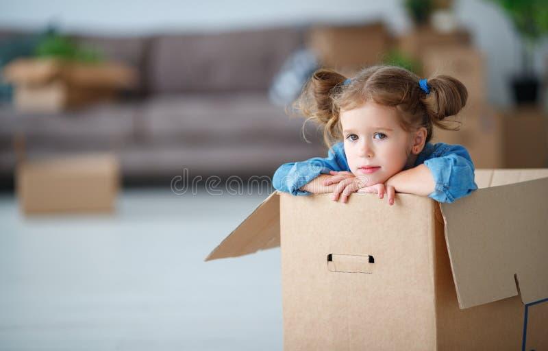 Menina da criança que senta-se na caixa para mover-se para o apartamento novo fotografia de stock
