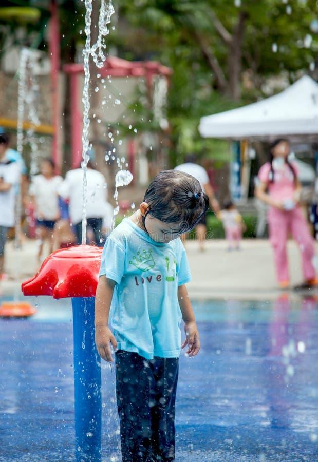 Menina da criança que tem o divertimento a jogar com água na fonte do parque imagens de stock royalty free