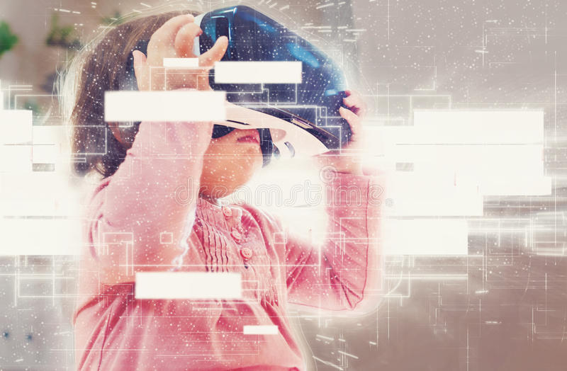 Menina da criança que usa uns auriculares da realidade virtual imagem de stock