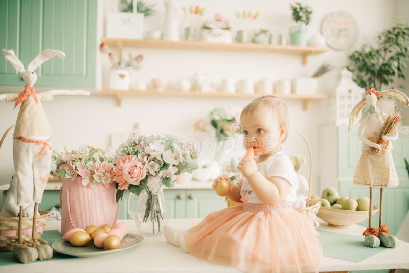 A menina da criança senta e come uma cenoura entre as decorações de easter imagem de stock