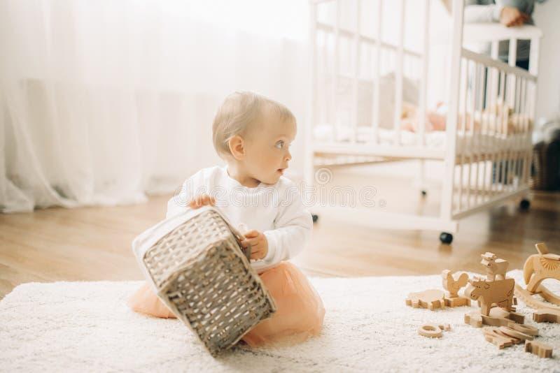 A menina da criança senta-se na esteira e nos jogos com cesta foto de stock royalty free