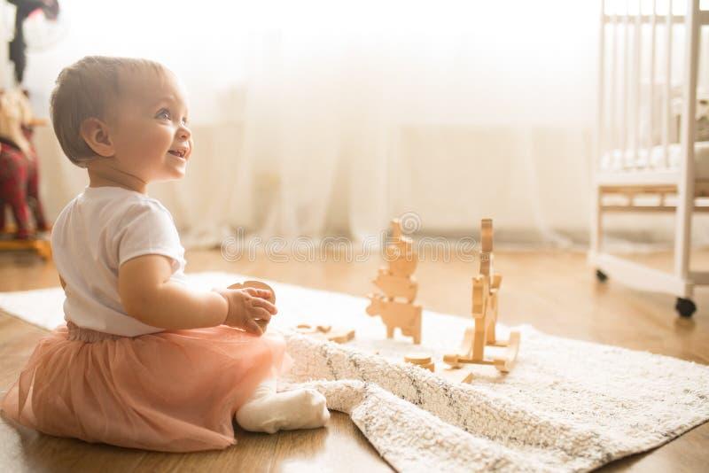 A menina da criança senta-se na esteira e nos jogos foto de stock royalty free