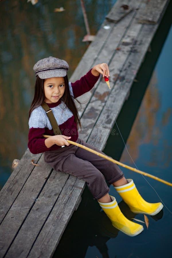 A menina da criança senta-se na ponte de pesca de madeira e trava-se peixes fotografia de stock royalty free