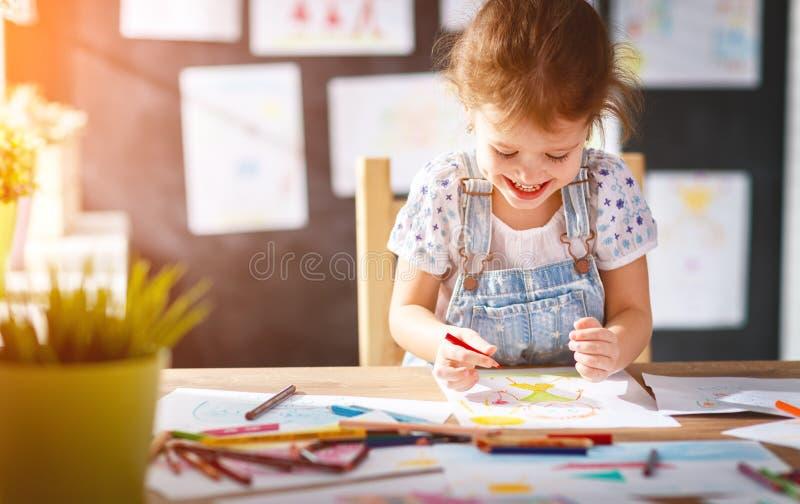 A menina da criança tira com lápis coloridos fotografia de stock