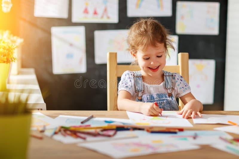 A menina da criança tira com lápis coloridos fotos de stock