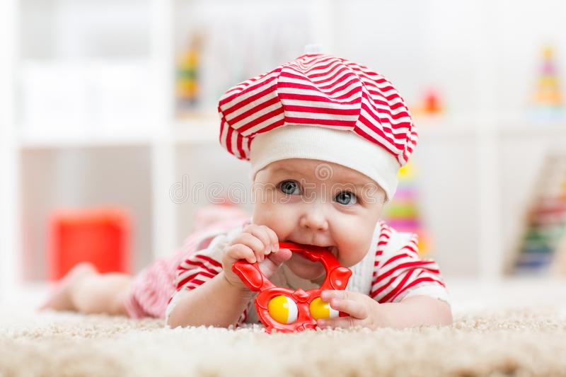 A menina da criança weared o costue que morde um brinquedo que encontra-se em um tapete em casa imagens de stock