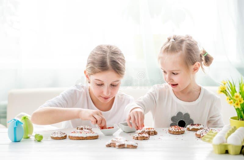 Menina da crian?a que decora cookies da P?scoa fotografia de stock royalty free